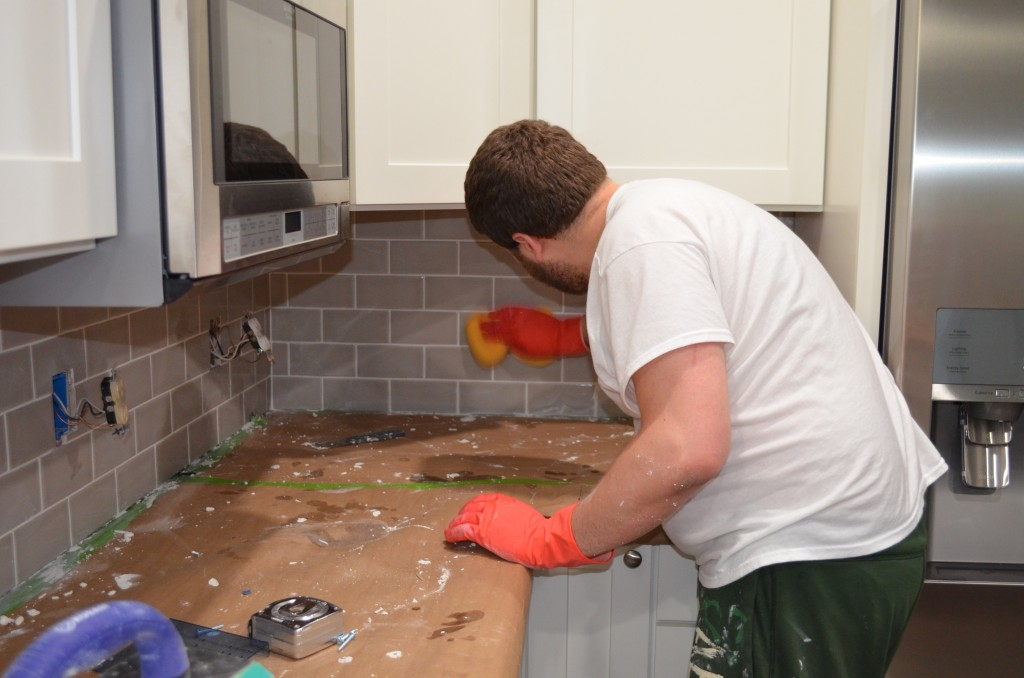 Wiping the tile clean with a sponge to make grout clean-up easier after it dries.